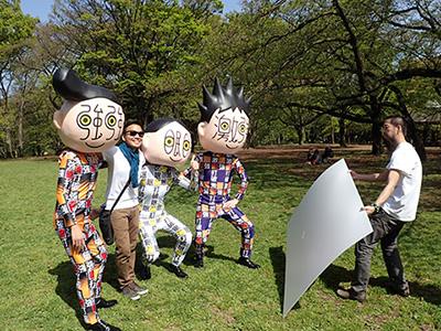 知らない人との記念写真にレフをあてる岩沢さん。