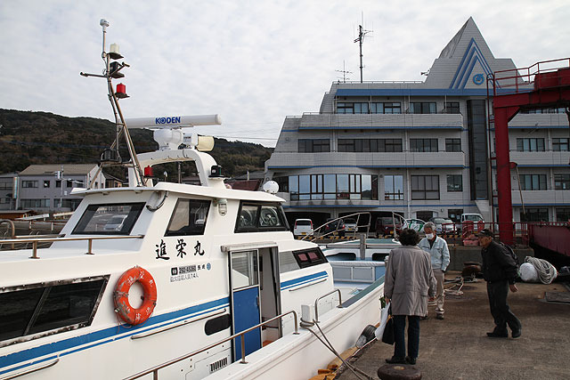 By taking this ship.  The building behind the ship is a hotel & a waiting room for a ferry & a city hall branch office.  A fishing rod was leaning against the wall in the waiting room.
