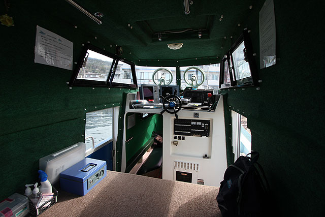 Inside the ship.  Enter inside and suddenly there is a wheelhouse.  Behind it, there is a space where you can take your shoes off and sit down.