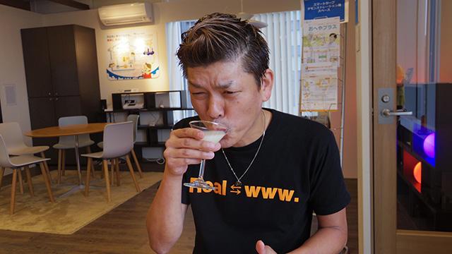 カクテルグラスでカルピス原液を飲む横山さん