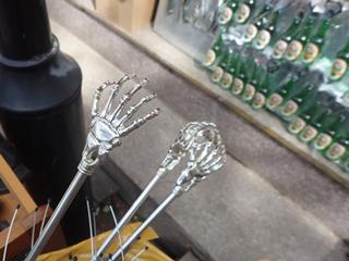 お土産やさん、孫の手が骨だけになったような物体の背後にビール瓶が山積み