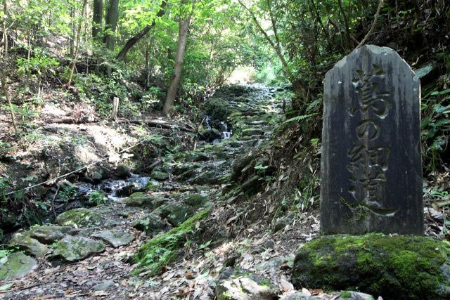 坂を下り切ったところで未舗装路は終わった。こちら側の入口には立派な石碑が