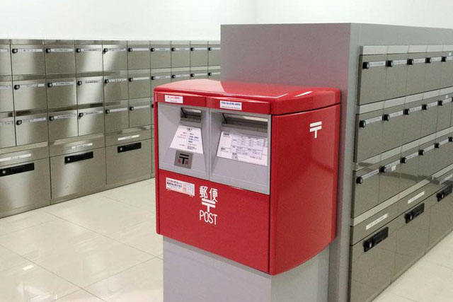 別の場所で類似の集合ポストも見つけたのだが、そこでは普通の郵便ポスト(郵便差出箱13号)が、私設ポストとして使われていた。ほんとにポストは何でもいいんだな、というのがよく分かる