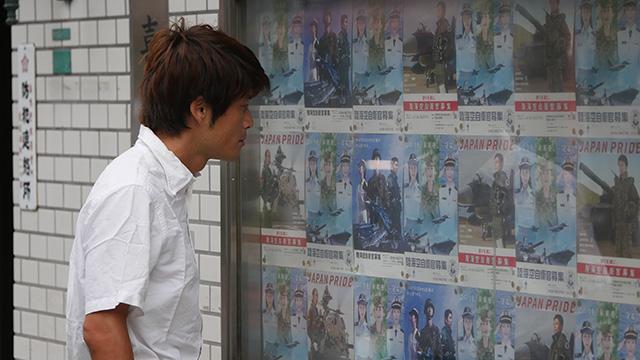 写真5 ポスターの前で立ってもらった。「自衛隊に入るのだろう」「店をたたんで自衛官になるのだろう」ポスターの意味に印象が引っ張られる結果となった