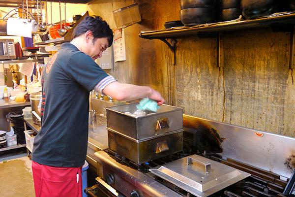 店舗どころかいきなり厨房にお邪魔してしまった。茶碗蒸しを蒸す「和Cafe&Dining えんや」代表の清水さん。