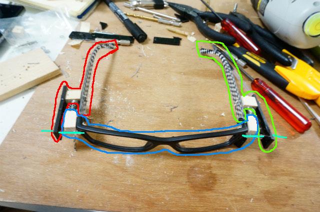 ここまでの仕組み。メガネは左右のツルと正面のフレームの3つのパーツに分かれている。レンズ左右の針金(図の水色の線)がストッパー(かんぬき)になっていて、抜くとバネの力で飛び出す。