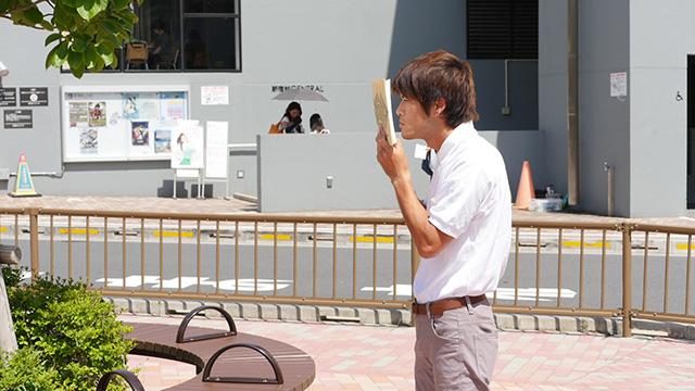 写真5(本を読む-近い姿勢) 「文字を初めて見た人のようだ」「なにかを嗅いでいるのか」