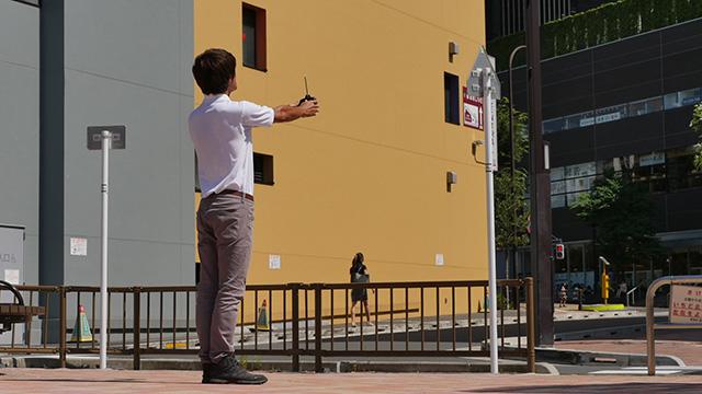 写真27(ラジコンのコントローラーを持つ-直線的な身体で) 「ビルを動かそうとしている」「頭がひどくわるそうである」
