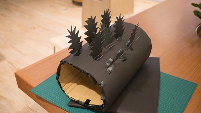 ダンボールに黒い模造紙を重ねたもので、板と筒を作る。そこに背びれを貼っていく。