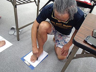 紙の上に足を置いて垂直に立てたペンで足の外周をなぞる。