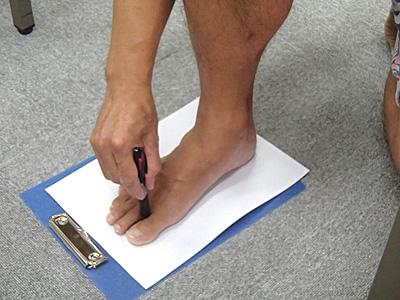 前の紐を通す穴を開ける位置に印をつける。足にフィットするように、なるべく指の谷間の底に近い位置につけるのがコツ。