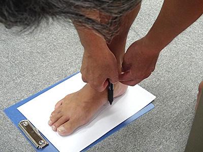 くるぶしの前の所に触るように垂直にペンを下して側面の紐を通す穴の位置を印する。