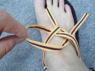 締め付け具合を調整しながら、輪を通した紐を引いて結び目を作り外側を固定する。続いて甲の上で内側に向かう2本の紐の下を通す。通した後に外側に向かう2本の紐の下を通して輪を作る。