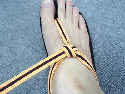 締め付け具合を調整しながら、輪を通した紐を引いて結び目を作り外側を固定する。