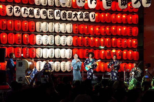大観衆を前に歌声を響かせる勝広師匠。ちなみに5000円払うと舞台の提灯に名前を書いてもらうことができ、スポンサー気分を味わうこともできる。
