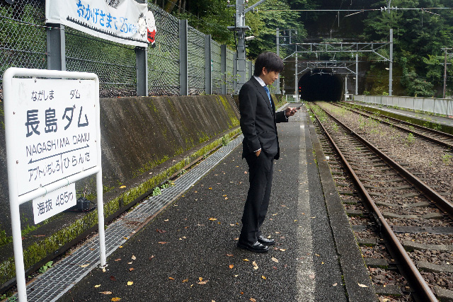 ふつうに駅で電車をまっているサラリーマン