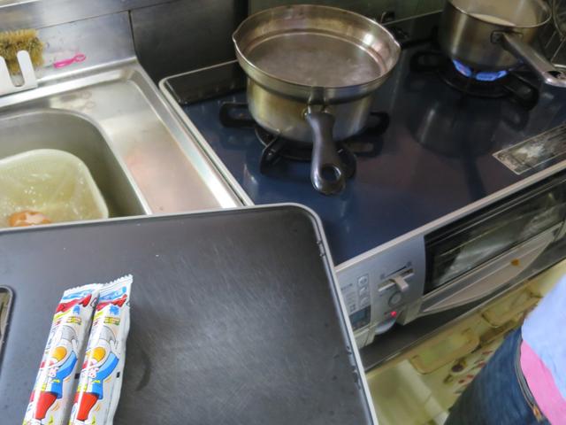まな板の上のうまい棒、そして奥に煮えたぎる鍋が