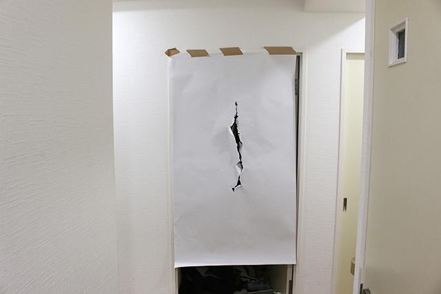 自宅のドアに模造紙を貼って撮影。これをネクタイにプリントする。
