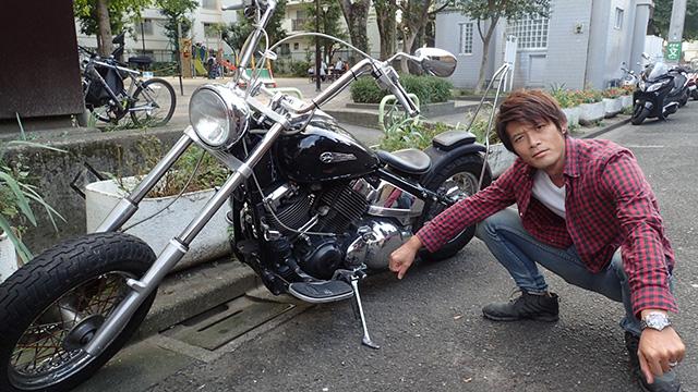 人のバイクの隣でしゃがむ