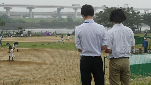 土手に立ち野球少年を眺めるシャツの男2人。手にしているのは…スピードガンだ! スカウトをやってみたら注目されて照れるということが判明しました。