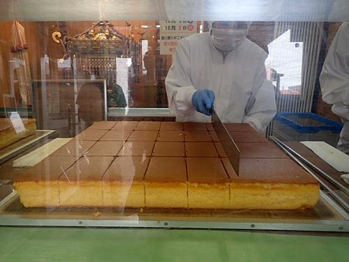 巨大な包丁で正確に切り分けられていくカステラ。切る前のカステラってこんなにでかいのか。マグロの解体と違って、どこをとっても均一だ。