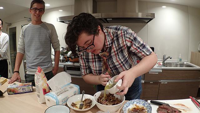 溶けたバターにハーブとニンニクをまぜて、ステーキ丼にだぶだぶとかけるアメリカ人と、さすがに若干引き気味に見えるオランダ人。