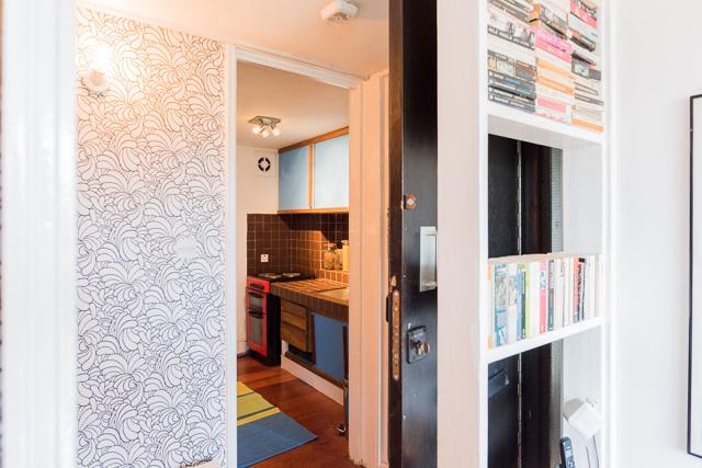 居間からキッチン・玄関方向を振り返った様子。黒いのが玄関の扉。いまは開け放ってる状態。キッチン横の壁紙もかわいい。