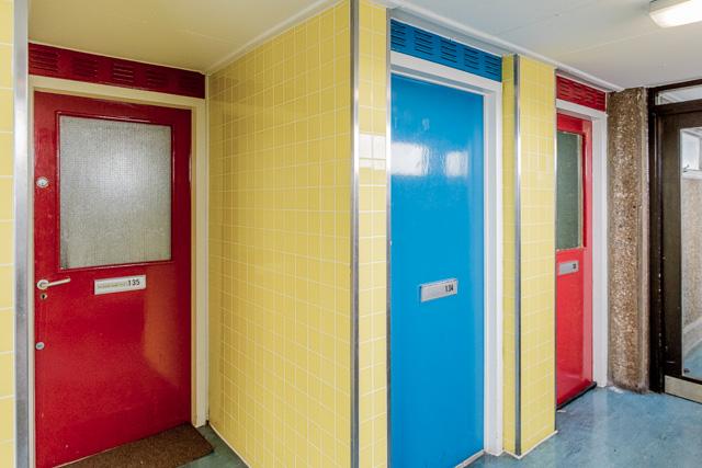 この3戸だと、一番左の部屋は中に入っても階段なしでこのフロアに部屋が配置されている。真ん中のブルーの扉の部屋は、入ると下り階段があって、ひとつ下の階に部屋がある。一番右は入ると上り階段がある、Stephan さんちと同じタイプ。
