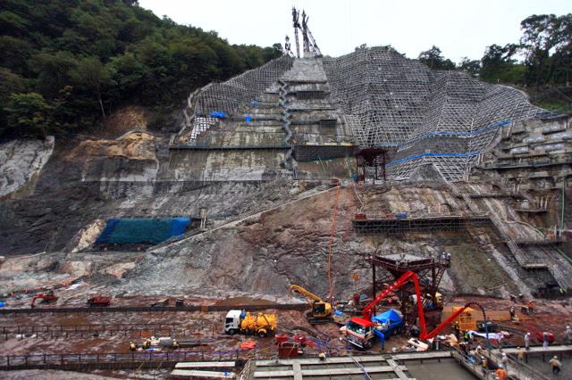 向かいの斜面にダムのシルエットがなんとなく浮かび上がっている(マウスオンで堤体断面を表示します)