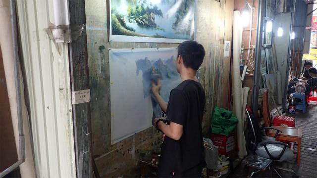 山水画っぽい絵を模写してる青年