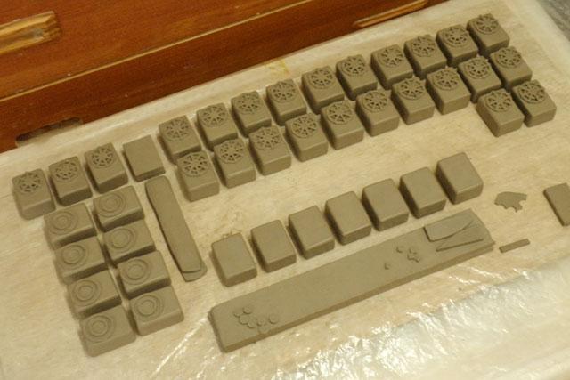 制作の様子は、都度写真で見せてもらっていた。これは陶土で成形している途中。ただの直方体に三菱型のグリルが付けられ、徐々に室外機が出来上がっていく様子が見て取れる。最初のフィギュア化の際はパソコンで3Dデータを作ったが、あれを手でやる場合はこうなるのだ