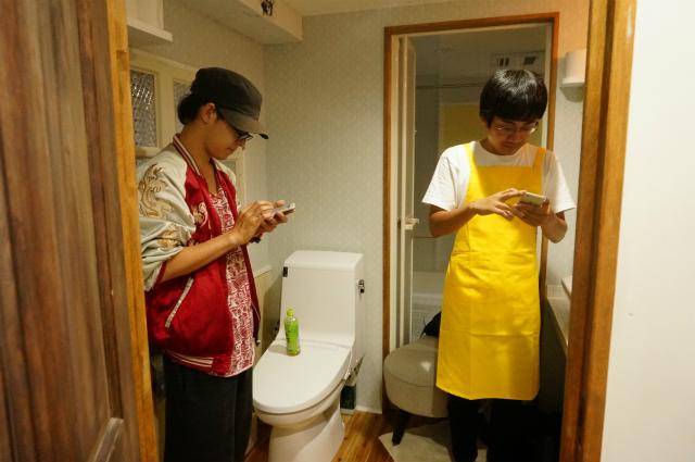 携帯でTwitter見ているように見えるが、左の人は曲の頭出しをしており、右の人はトイレで振り付けの練習をするという貴重な体験を写真に収めている