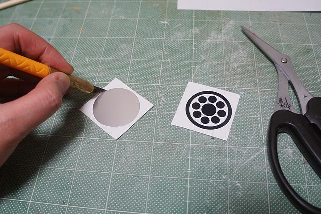 「丸に九曜」紋をラベル印刷して、丸い板に貼る。