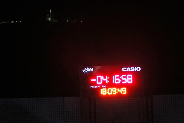 X-4時間前。向こうにぼんやりとライトアップされたロケットが見える。