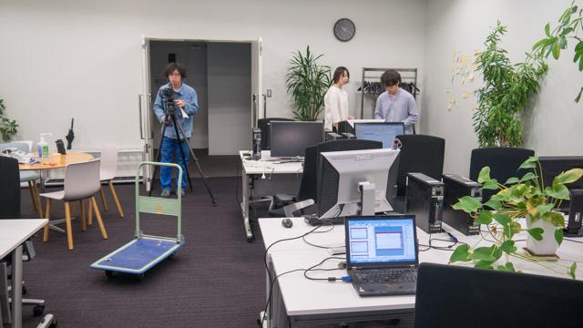 撮影の大半を会社でやることにしよう、と大きな会議室をみんなで会社にする。パソコンや傘立てなど運び入れる。植物を置くとオフィス化するという逆説的なことが起こった