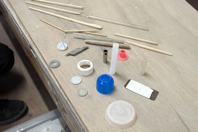 そのほかの道具たち。丸いものはクッキー型みたいに、車輪を切り抜くときなどに使う。割り箸やギザギザしたもの、硬貨などは、細かい模様を書き込むのに役立つ。とにかく使えるものは何でも使うとのことで、道具だけ見ると完全に「モデラー」である