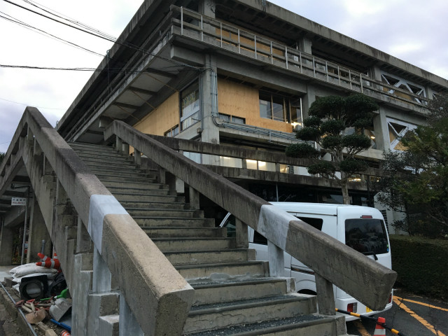 市役所の崩れ落ちた階段の手すり部分は修復中