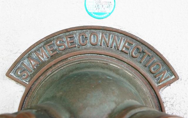 プレートの表記に英語「SIAMESE CONNECTION(サイアミーズ コネクション)」が用いられていたのが昭和20年代。20年代後半から30年代にかけてカタカナ~日本語表記に移行が進み、現在では「送水口」と表記されている。つまり、英語表記のものは昭和30年以前に作られた可能性が高い。