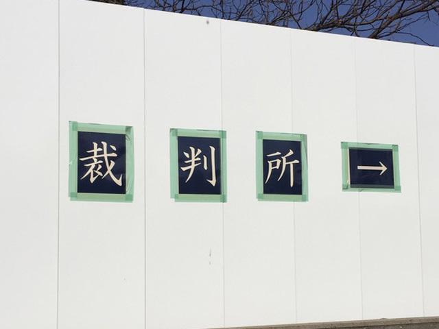 仮設の裁判所の、看板も仮設だ。紙だ。(下に続く)