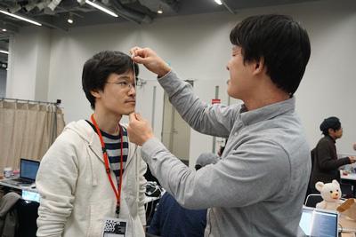 パネルに顔の大きさの穴を空けるのに定規がなく、ケーブルで長さを測る図。