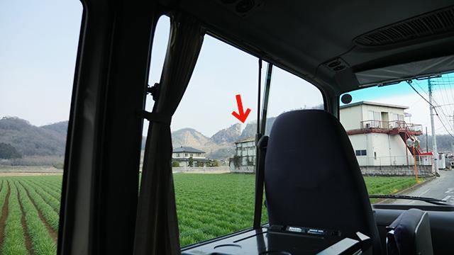 バスから見える岩舟山方面。矢印のあたりは3.11の地震でばっきりV字に山が欠けたらしい。