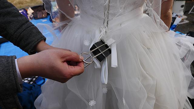 ドレスの裾とベールが風で暴れるのを固定するため、こんなこともあろうかと持ってきていた巨大ダブルクリップを使用する。文房具、便利。