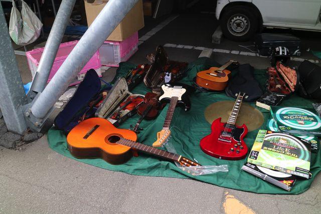 バイオリン、エレキギター、アコースティックギター、蛍光灯…という謎の並び。フリーマーケットっぽいな。