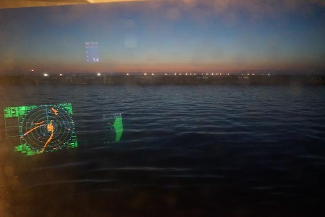 朝焼けをバックに港を出てゆく船の灯が連なる。壮観!