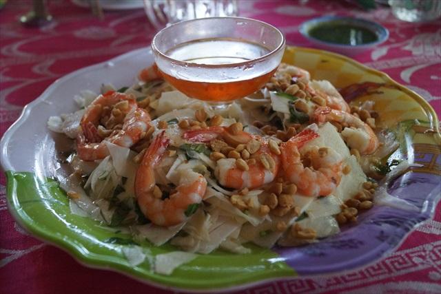ベトナム料理では定番の蓮の茎が入ったサラダだが、白い板状のものはココナッツの実を削いだものだ。大根の桂剥きのような食感だが、特有の甘い風味がする。