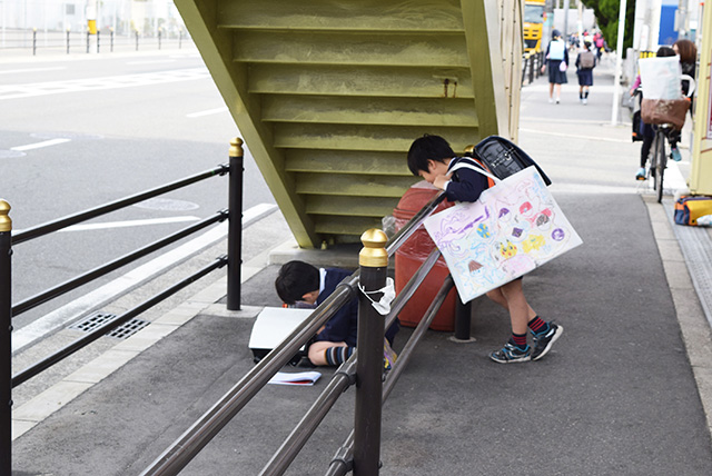 下校時間の小学生が歩道橋の下で勉強していた。