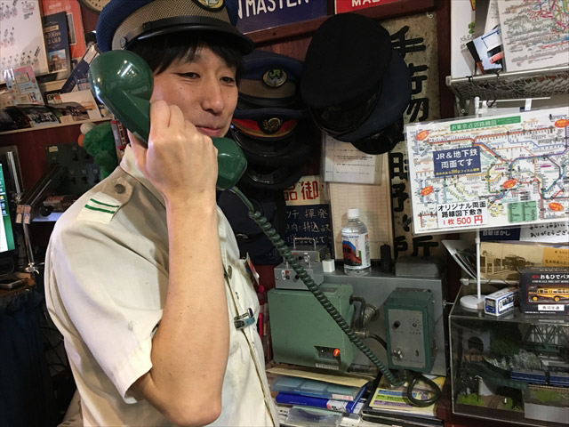 駅長(店長)の渡邉さん。この機材、ちゃんと天井のスピーカーにつながっています