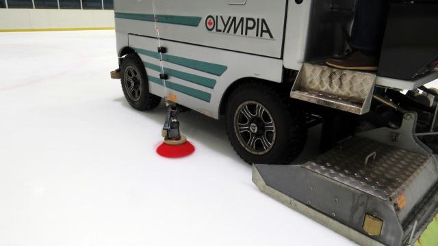 フェンスぎわの氷をかき出す「ボードブラシ」。