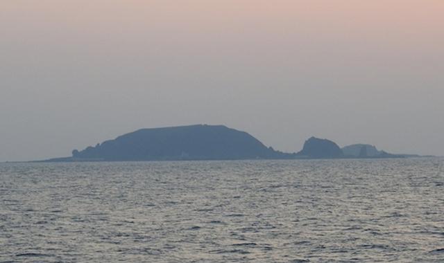 朝焼けと共に小宝島が見えてきた。「妊婦が横になったように見える」といわれる遠景。