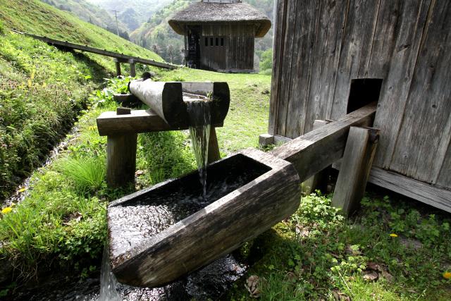 水の力を利用してアワやヒエを杵を突く「バッタリ小屋」が再現されている